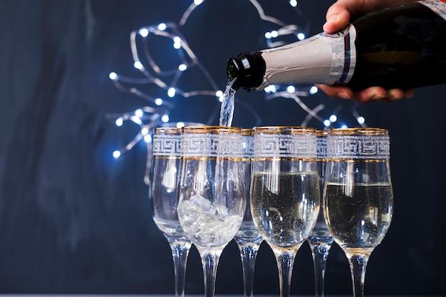 Menschliche hand, die champagner in das transparente glas an der party gießt