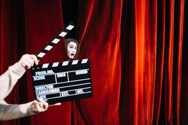 Menschliche hand, die clapperboard vor männlichem pantomimekünstlergesicht hält