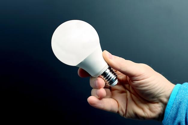 Menschliche hand, die die mitgelieferte led-lampe auf einer dunkelheit hält. strom- und led-industrie