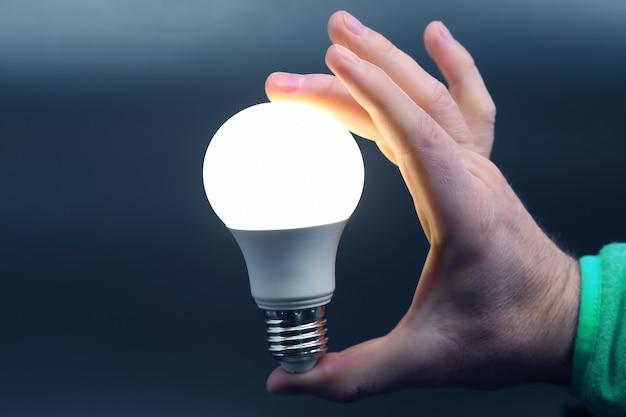 Menschliche hand, die die mitgelieferte led-lampe auf schwarz hält. strom- und led-industrie