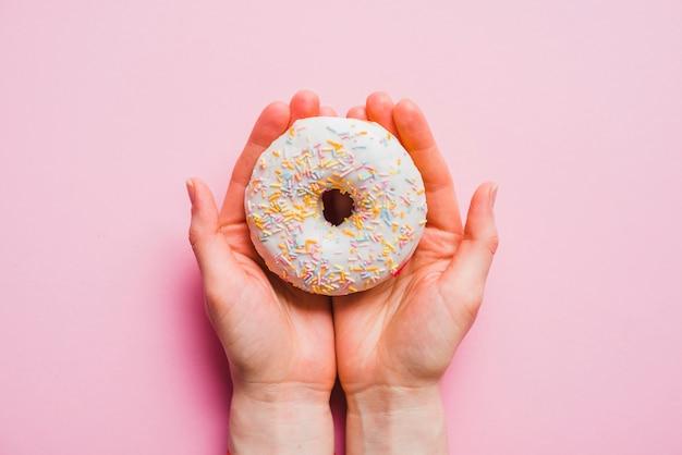 Menschliche hand, die donut auf rosa hintergrund hält