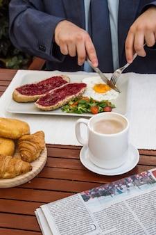 Menschliche hand, die ei mit gabel- und buttermesser im restaurant schneidet