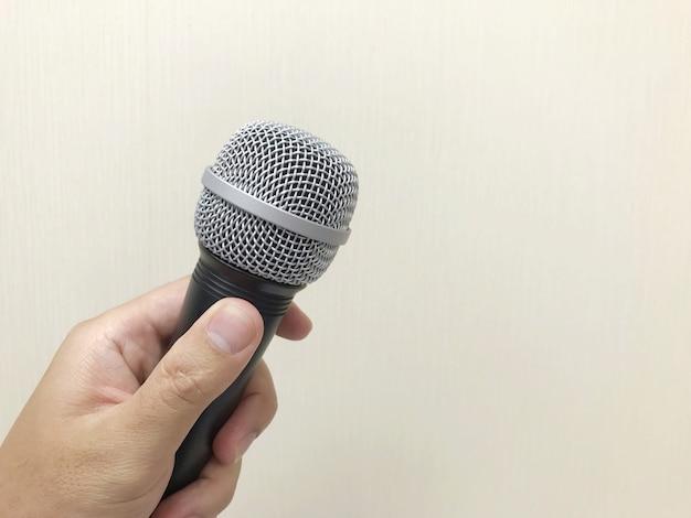 Menschliche hand, die ein mikrofon hält, um sich auf das sprechen oder das singen vorzubereiten.