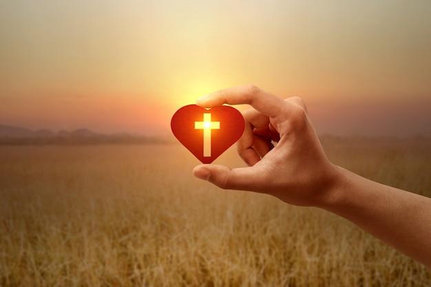 Menschliche hand, die ein rotes herz mit einem christlichen kreuz mit einem sonnenaufgangshimmel hält