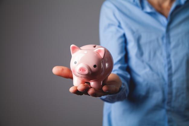 Menschliche hand, die ein sparschwein schützt