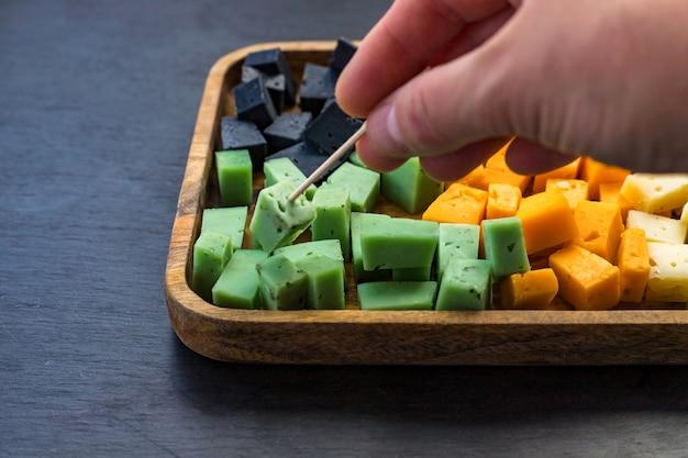 Menschliche hand, die ein stück käse mehrfarbig auf einem holztablett auf schwarzem schieferhintergrund sticht