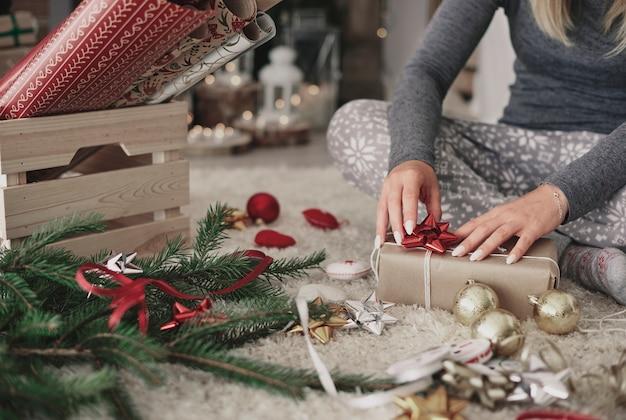 Menschliche hand, die ein weihnachtsgeschenk verziert