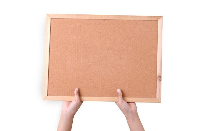Menschliche hand, die eine braune korkplatte in einem rahmen lokalisiert über weißer wand hält
