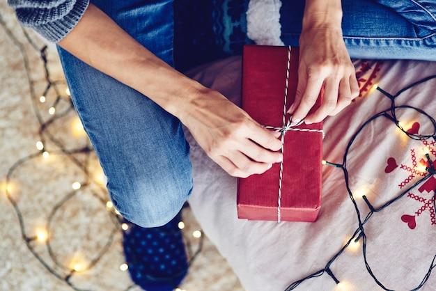 Menschliche hand, die eine schnur an einem geschenk bindet