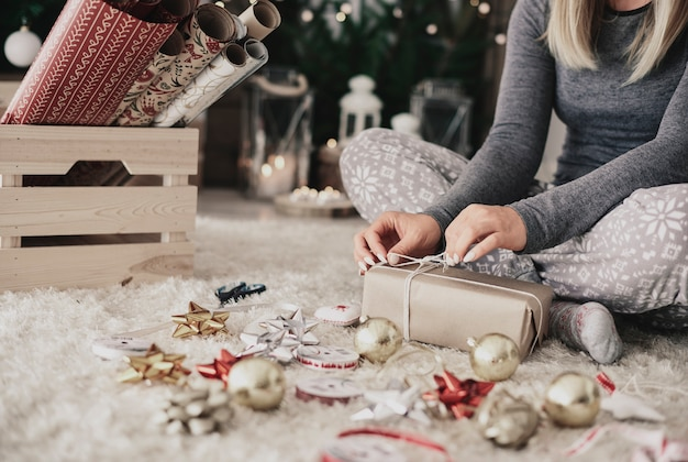 Menschliche hand, die eine schnur auf weihnachtsgeschenk bindet