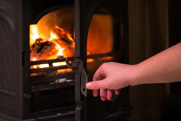 Menschliche hand, die eine tür des brennenden kamins mit holzbränden öffnet, die innen brennen.