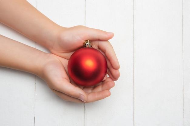 Menschliche hand, die eine weihnachtskugel auf hölzernem weiß hält