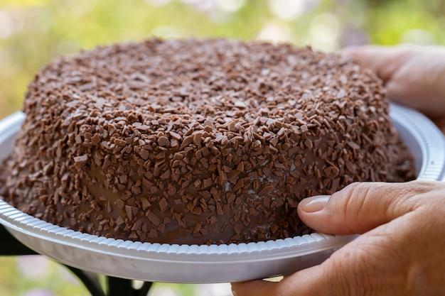 Menschliche hand, die einen perfekten und köstlichen brigadeiro- / schokoladenkuchen hält.