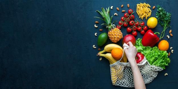 Menschliche hand, die einen schnurbeutel mit gesundem vegetarischem essen hält. vielfalt an gemüse und obst