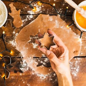 Menschliche hand, die form für keks hält
