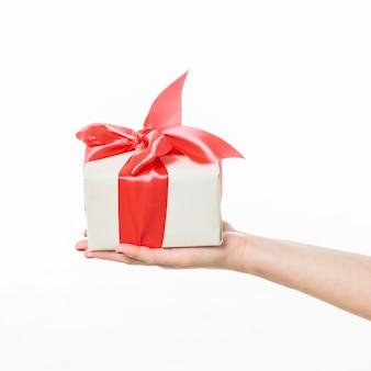 Menschliche hand, die geschenkbox auf weißem hintergrund hält