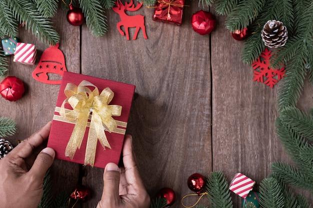 Menschliche hand, die geschenkbox mit weihnachtshintergrund mit dekorationen auf hölzernem brett, konzept des festivals des neuen jahres hält.