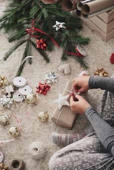 Menschliche hand, die geschenke an weihnachten vorbereitet