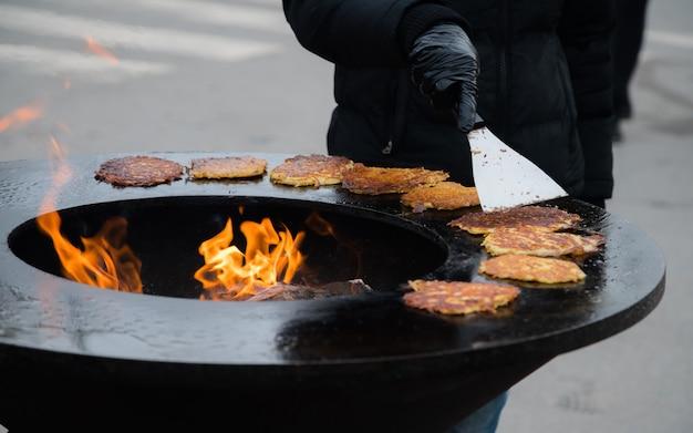 Menschliche hand, die goldene kartoffelpfannkuchen an der stadtmesse draußen kocht. Premium Fotos