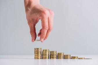 Menschliche Hand, die goldene Münzen auf reflektierendem Schreibtisch stapelt