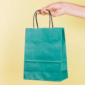 Menschliche hand, die grünbucheinkaufstasche auf gelbem hintergrund hält