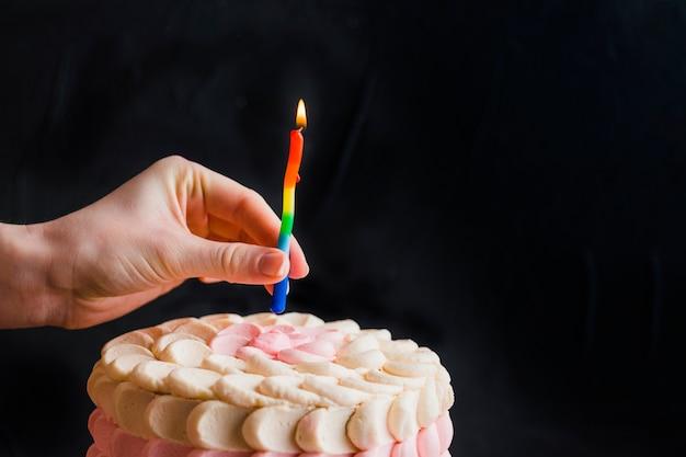 Menschliche hand, die kerze auf kuchen setzt