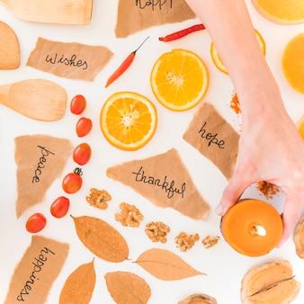 Menschliche hand, die kerze nahe früchten, anmerkungen und blättern hält