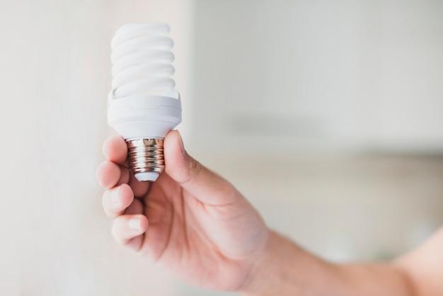Menschliche hand, die kompakte leuchtstoff glühlampe hält