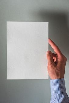 Menschliche hand, die leeres weißbuch hält
