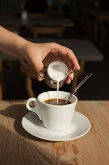 Menschliche hand, die milch in den schwarzen kaffee in der cafeteria gießt