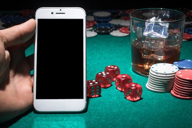Menschliche hand, die mobiltelefon auf kasinotabelle hält