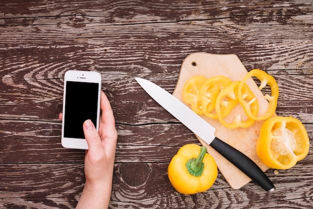 Menschliche hand, die mobiltelefon mit scheiben des gelben grünen pfeffers auf hackendem brett mit messer über dem hölzernen schreibtisch hält