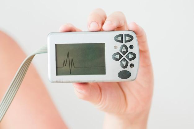 Menschliche hand, die monitor mit kardiogramm hält