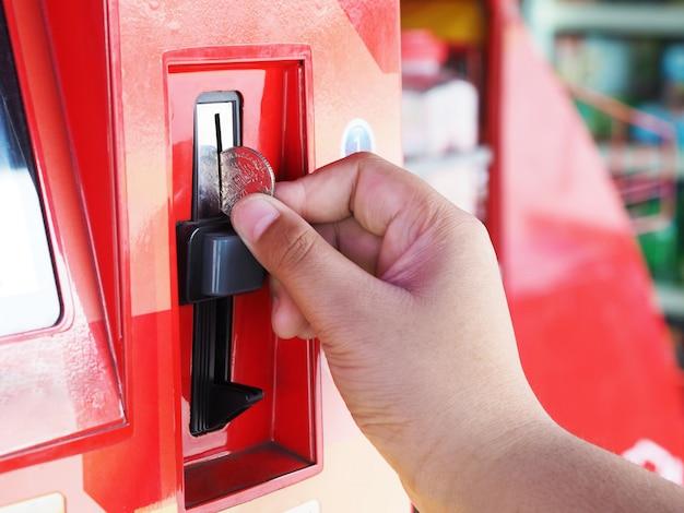 Menschliche hand, die münze in automaten einfügt