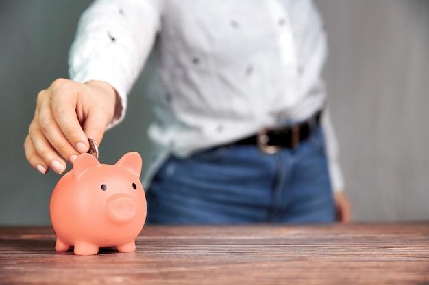 Menschliche hand, die münze in rosa sparschwein setzt