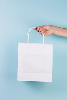 Menschliche hand, die papiereinkaufstasche hält