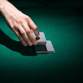 Menschliche hand, die pokerkarte im kasino hält
