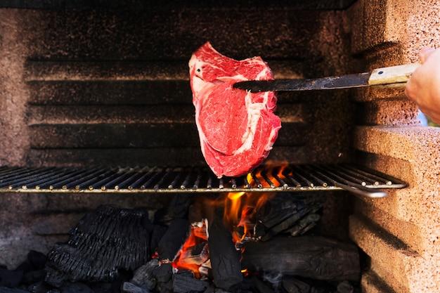 Menschliche hand, die rohes fleisch auf grillgrill kocht