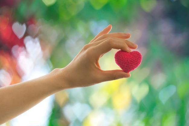 Menschliche hand, die rotes herzformzeichen auf schönem hintergrund hält.