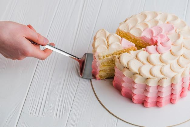 Menschliche hand, die scheibe des kuchens mit spachtel nimmt