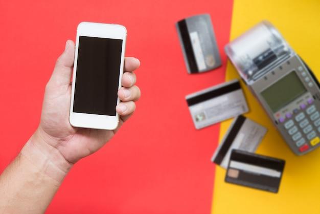 Menschliche hand, die smartphone für zahlung mit unscharfer kreditkarte und kreditkartemaschine auf rotem und gelbem hintergrund hält.