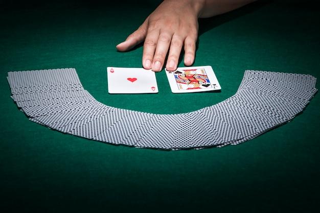 Menschliche hand, die spielkarte auf schürhakentabelle berührt