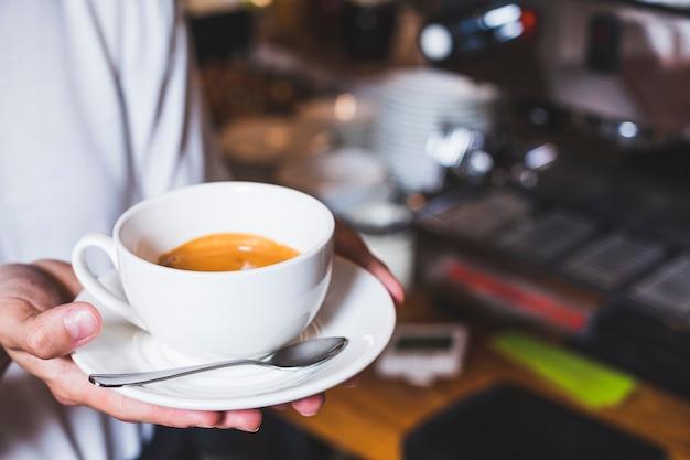 Menschliche hand, die tasse kaffee in der cafeteria hält