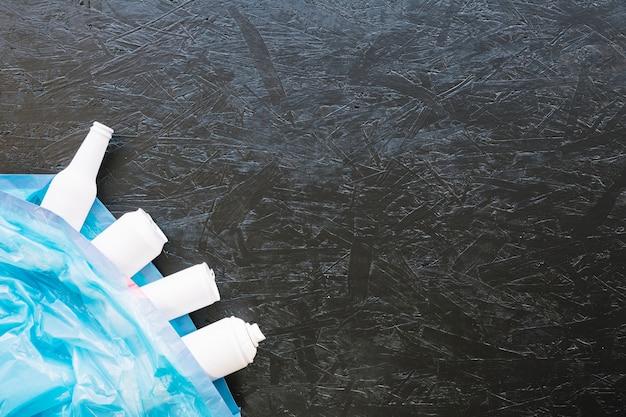 Menschliche hand, die weiße aerosoldose gegen schwarzen hintergrund hält