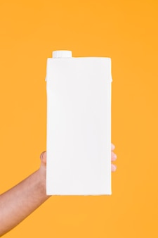 Menschliche hand, die weißen milchkasten auf gelbem hintergrund anhält
