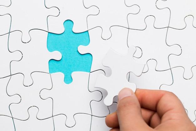 Menschliche hand, die weißes puzzlespiel in leeren raum einfügt