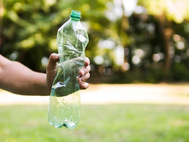 Menschliche hand, die zerquetschte plastikflasche an draußen hält