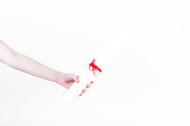 Menschliche hand, die zertifikat mit rotem band hält