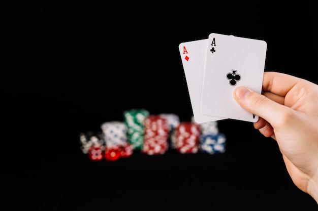 Menschliche hand, die zwei spielkarten der asse hält