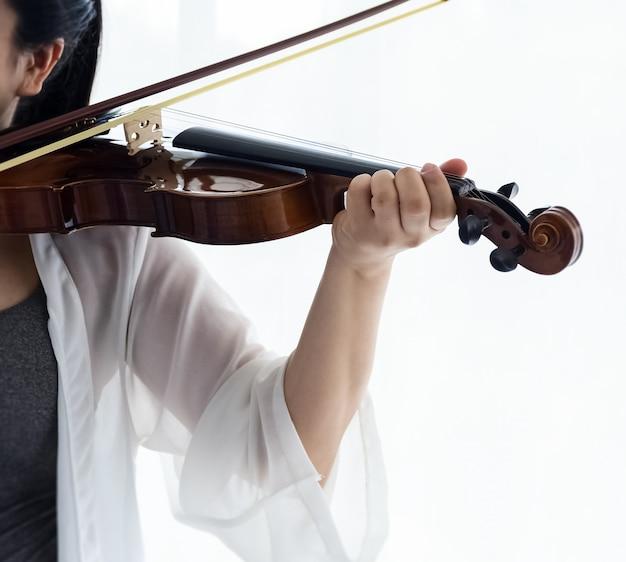 Menschliche hand drücken saite der violine, zeigen, wie man das akustische instrument spielt